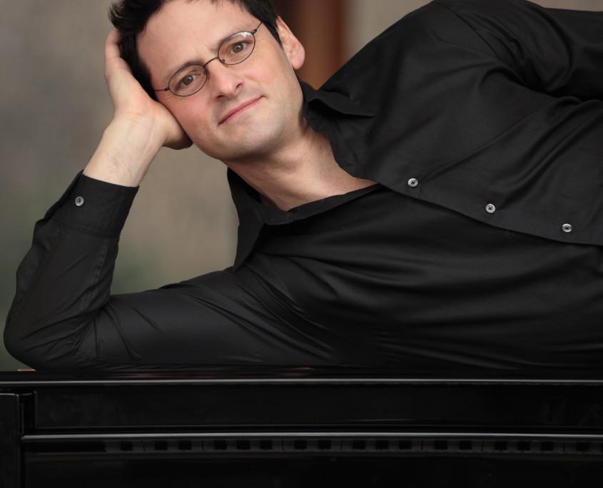 Pianist Tobias Forster, liegend auf Flügel, Porträt Pressefoto Hochformat