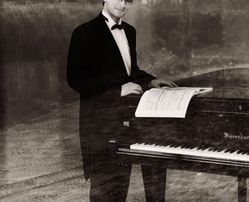 Pianist Tobias Forster, stehend am Flügel, Pressefoto